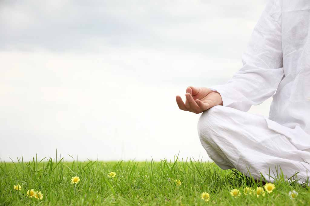 Woman sitting in meditative lotus position on meadow